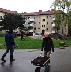 Personer jobbar med jord på gården